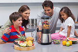 Smiling family using a blender