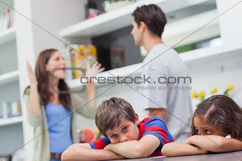 Couple arguing behind their children