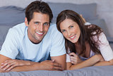 Delighted couple lying on bed