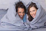Smiling couple having fun wrapped in their duvet