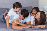 Happy family having fun on the bed