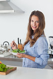 Woman in the kitchen holding a salad bowl