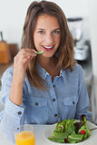 Pretty woman eating a salad with a glass of orange juice