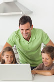 Man and his children using a laptop together