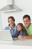 Portrait of a family using a laptop in the kitchen