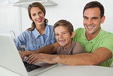 Family using a laptop in the kitchen