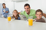 Portrait of a father and his children having breakfast