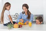 Woman cutting an orange for her children