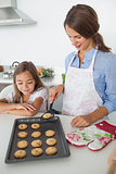 Mother giving a homemade cookie to her daughter