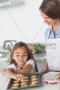 Little girl grabbing a cookie from a baking pan
