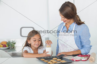 Little girl dunking a cookie into a glass of milk