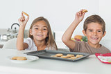 Siblings raising homemade cookies