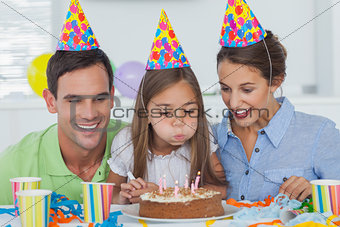Little girl blowing out her candles