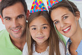 Parents and daughter wearing a party hat