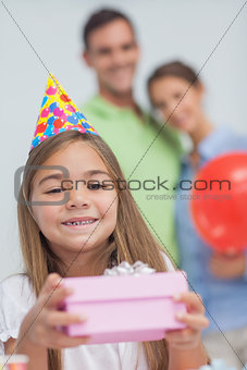 Little girl holding a birthday present