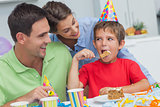 Little boy eating a birthday cake with parents