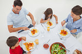Overview of a family eating pasta with sauce and salad