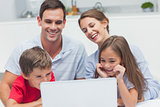 Cheerful parents and children using a laptop