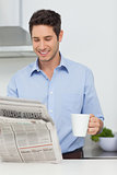 Man with a cup of coffee reading a newspaper
