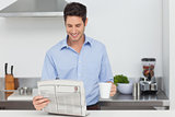 Man reading a newspaper in the kitchen
