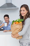 Attractive woman holding groceries bag