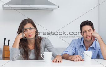 Tired couple sitting at the table with a cup of coffee