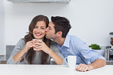 Man embracing wife who is holding a cup of coffee