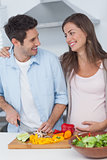 Pregnant woman looking at husband chopping vegetables