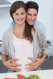 Man holding the belly of his pregnant wife