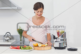 Pregnant woman cutting fruits in the kitchen