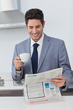 Businessman reading a newspaper and drinking a coffee