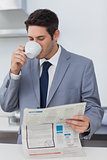 Businessman drinking a coffee and reading a newspaper