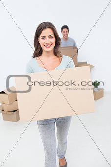 Attractive woman holding boxes in her new house