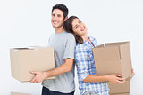 Wife and husband carrying boxes in their new house