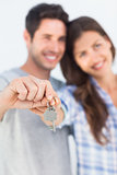 Man and wife presenting a key with a house keychain