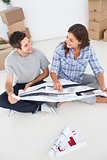 Happy woman and her husband looking at their house plans