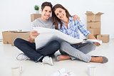 Portrait of man and woman holding house plans