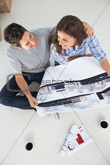 Overview of a husband and his wife holding house plan