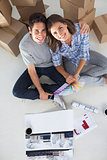 Overview of a man and his wife holding house plans