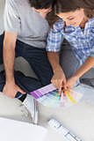 Woman pointing at color charts sitting in her new house