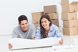 Couple lying on the floor and looking at house plans