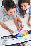 Couple looking at a color chart to decorate their house