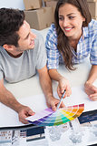 Happy couple looking at a color chart to decorate their house