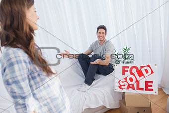 Man in his new house chatting with his wife