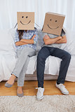 Couple sitting with cardboard boxes on head