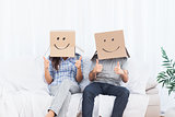 Couple sitting with cardboard boxes on head giving thumbs up