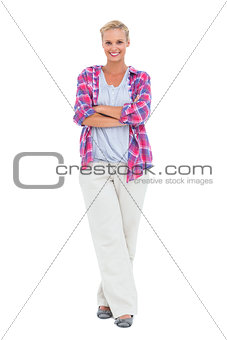Cheerful woman standing with arms crossed looking at camera