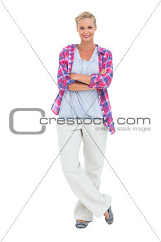 Happy woman standing with arms crossed looking at camera