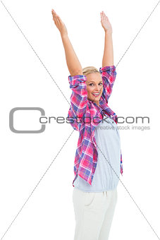 Happy woman standing with hands up in air
