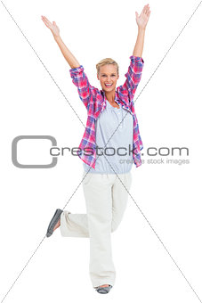 Excited woman standing with hands and foot up in air